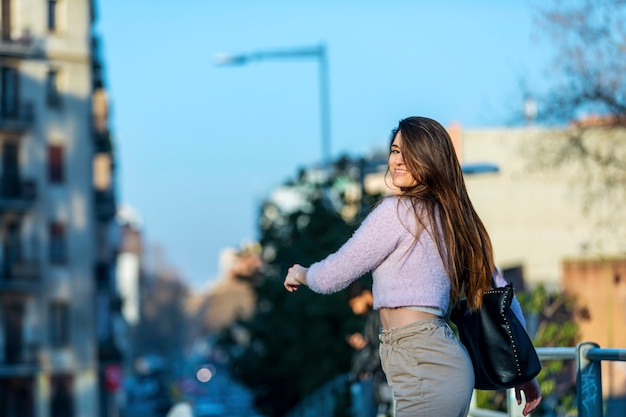 Rear view of smiling beautiful young woman walking in the street while looking back in a sunny day