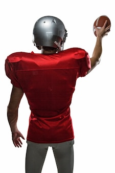 Rear view of sportsman in red jersey holding ball