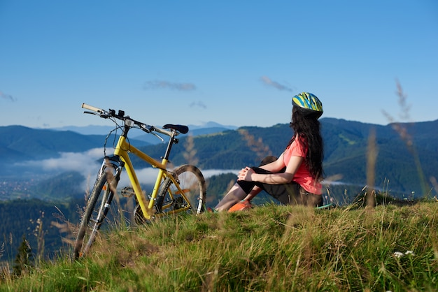 Rear view of sporty female cyclist sitting on the top of mountain near yellow bicycle
