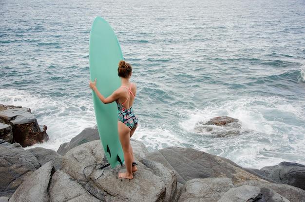 거리를보고 대서양의 바위 해변에서 서핑으로 서 멀티 컬러 수영복에 후면보기 스포티 한 소녀