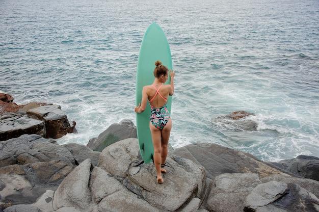 대서양의 바위 해변에서 서핑으로 서 멀티 컬러 수영복에 후면보기 스포티 한 소녀