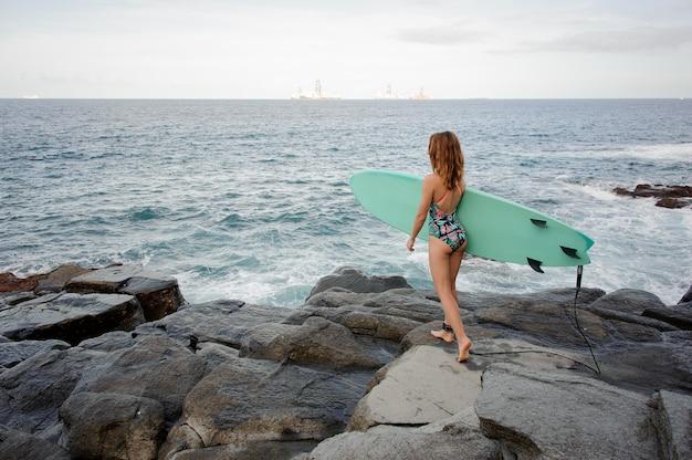 대서양 해변에서 바위에 서핑과 함께 산책하는 멀티 컬러 수영복에 후면보기 스포티 한 소녀. heathy 라이프 스타일의 개념