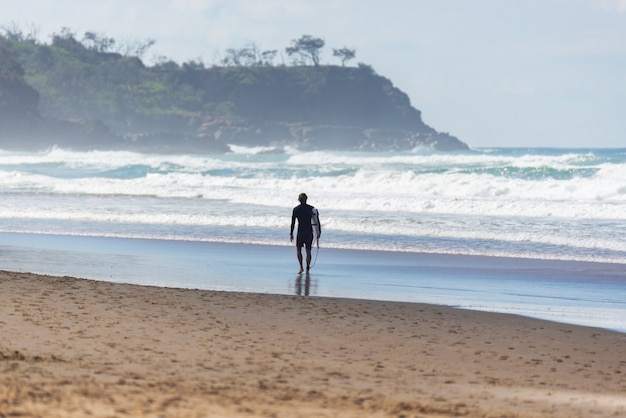 Rear view of surfer walking in an australian beach in summer.water deport concept.listro