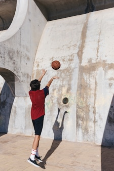 Rear view of a teenage boy practicing basketball