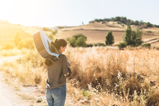 Rear view of a teenage girl holding guitar at outdoors