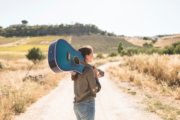 Rear view of a teenage girl standing on dirt road holding guitar