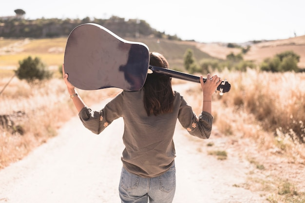 Rear view of a teenage girl with guitar standing on dirt road