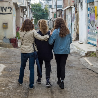 Rear view of three women walking in street, florentin, tel aviv, israel