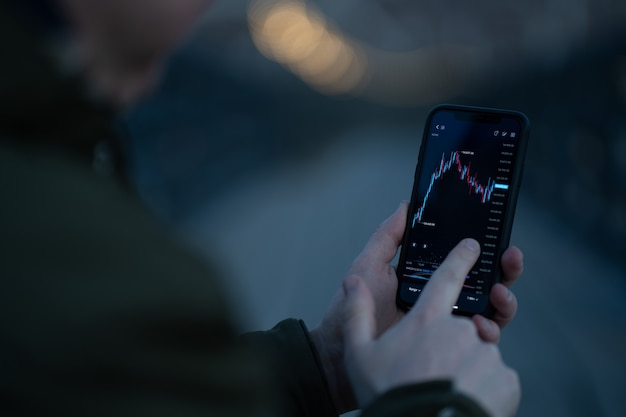 Rear view of trader monitoring stock market data in mobile app for online trading and investing on smartphone while standing outdoors, selective focus on hand touching screen with forex graph chart