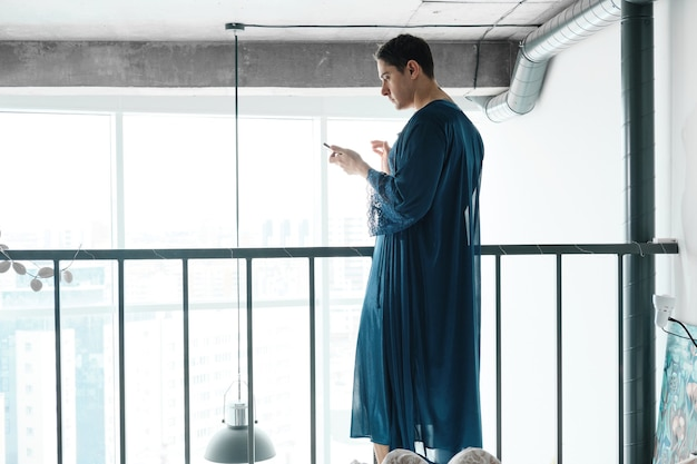 Rear view of transsexual in female dressing gown typing a message on his mobile phone while standing in the room
