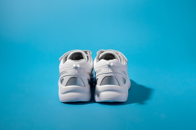 Rear view of two backs or heels of white sneakers for children with silver inserts on a blue paper b...