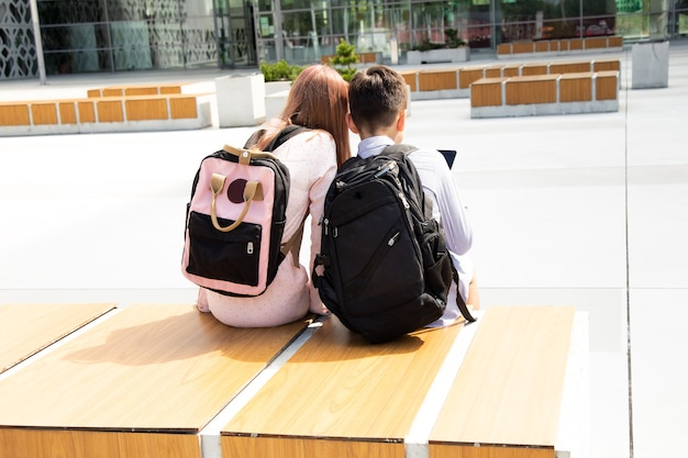 Rear view of two caucasian schoolgirl and schoolboy sitiing on wooden bench outdoors. they are wearing summer casual clothes and backpacks.