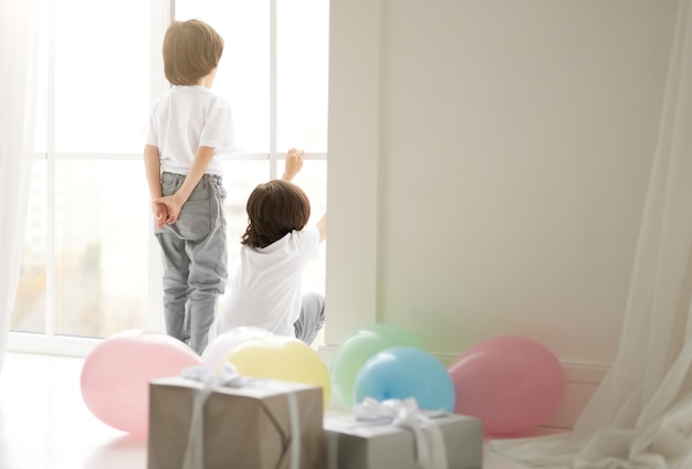 Rear view of two curious latin twin boys, children in casual wear playing at home, preparing for celebrating holiday with colorful balloons and giftboxes in the foreground. holidays, presents concept