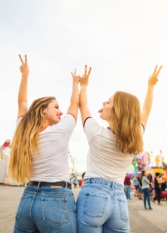 Rear view of two female friends gesturing peace sign