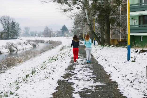 Rear view of two female friends jogging on road in winter