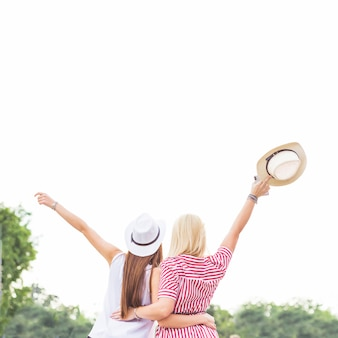 Rear view of two female friends raising their hands