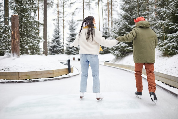 Rear view of two friends in warm clothing holding hands skating together in the park in winter day