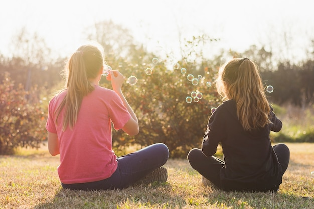 Rear view of two girl sitting on green grass blowing bubbles