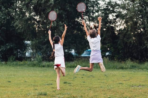 Rear view of two girls jumping in the park holding badminton