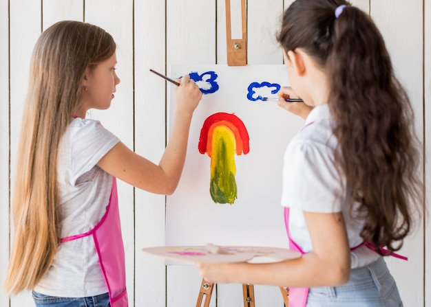 Rear view of two girls painting the clouds on canvas with paint brush
