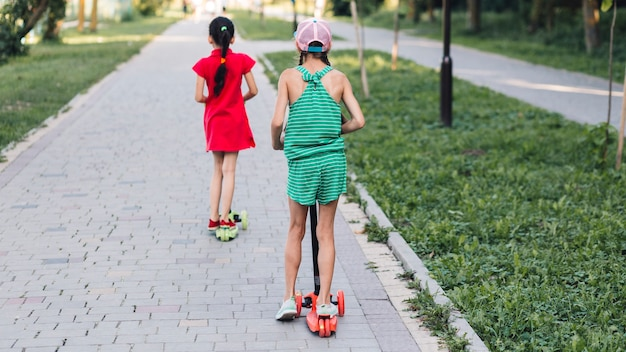 Rear view of two girls riding push scooter in park