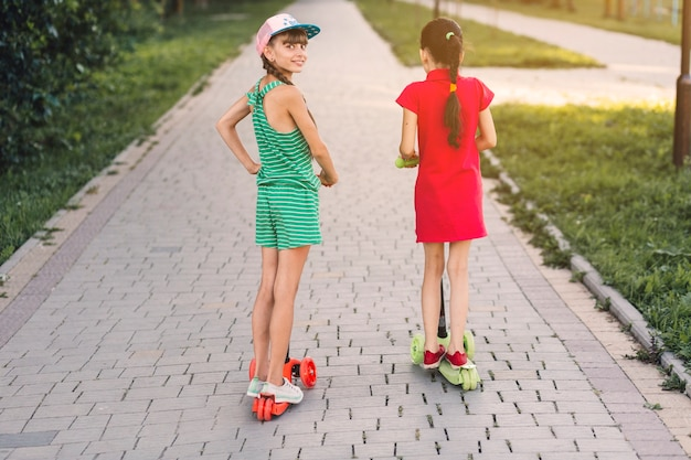 Rear view of two girls riding push scooter in the park