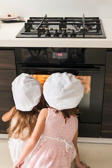 Rear view of two kids in chef hat looking at cookie tray in oven