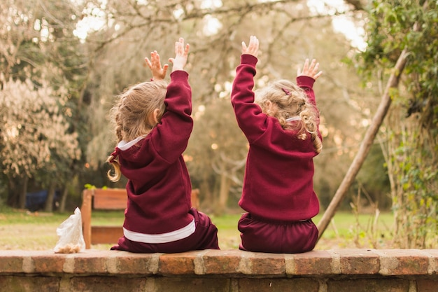 Rear view of two little girl sitting on bench raising their hands up