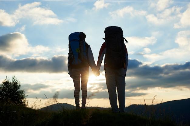 후면보기 배낭에 손을 잡고 두 사람이 구름과 하늘 아래 산에서 밝은 일몰을 즐길 수 있습니다. 산에서 낭만적 인 저녁