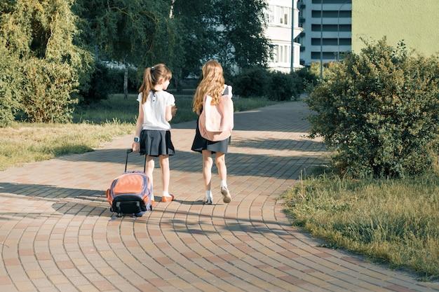 Rear view of two schoolgirl girlfriends elementary school