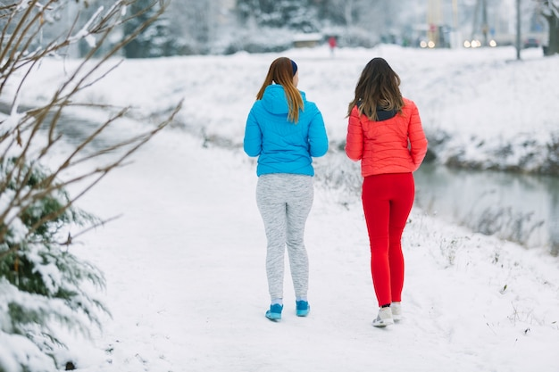 Rear view of two women walking together on frozen landscape in winter