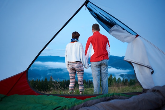 Rear view of two young people holding hands enjoy the morning scenery of the mountains on which the fog descended. view from inside a tent