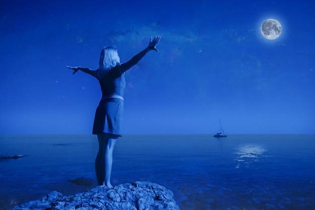 Неопознанная молодая счастливая женщина, вид сзади, стоит на камне, поднимает руки вверх. глядя на большую луну и спокойную чистую морскую воду на фоне пейзажа и ясного ночного неба. концепция полной луны