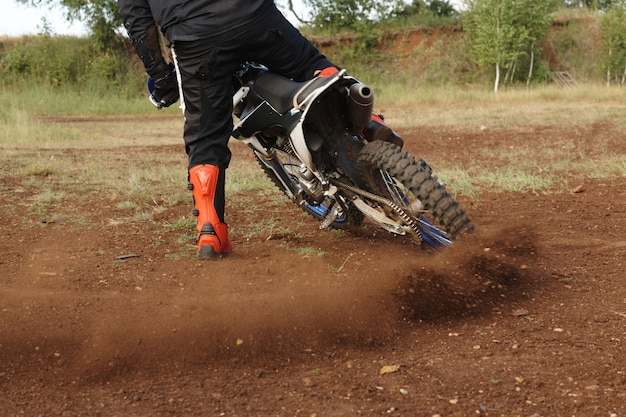 Rear view of unrecognizable man in red boots drifting motorbike on off-road track while stop it