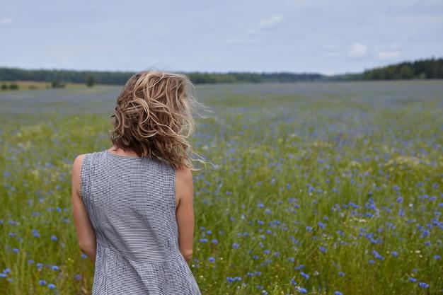 Vista posteriore di una ragazza snella irriconoscibile che gode di un bellissimo paesaggio, in piedi in mezzo al prato verde con fiori blu, i suoi capelli biondi ricci che ondeggiano al vento. donna che cammina all'aperto