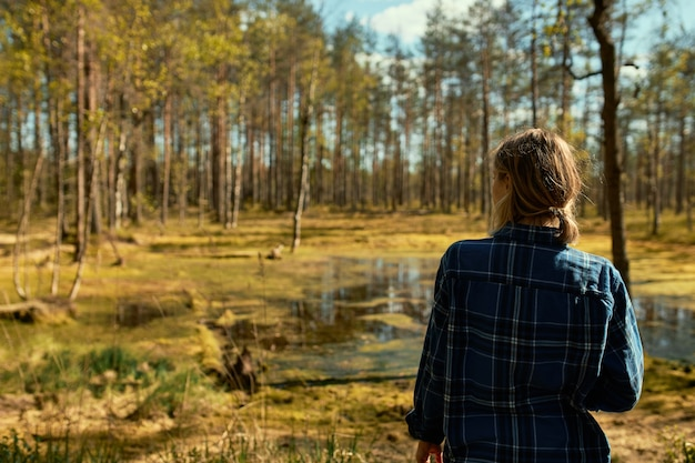 Rear view of unrecognizable young woman with ponytail having walk outdoors alone, posing in pine forest wearing coat, standing in front of swamp, enjoying beautiful sunny weather on spring day