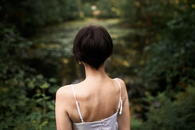 Rear view of unrecognizable young woman with short hair and slim body posing outdoors, standing in front of pond with her back to camera.
