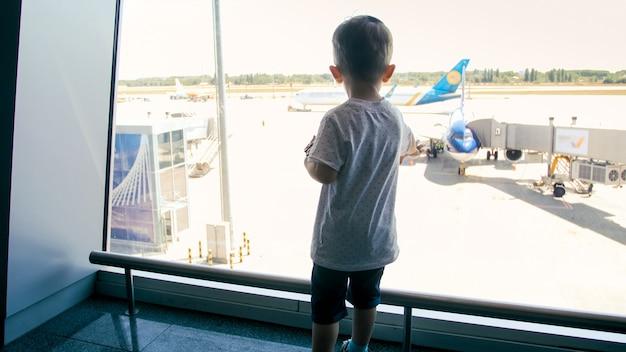 空港ターミナルの窓から見ているかわいい男の子の背面図。