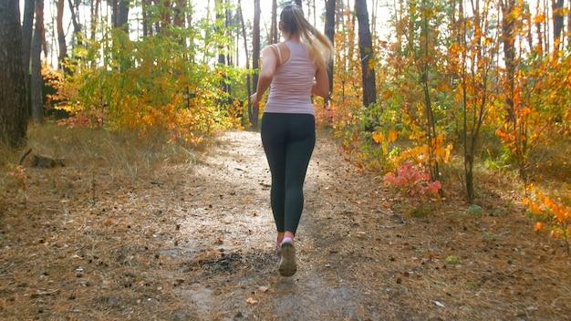 秋の森で走っている若いフィット女性の背面図。