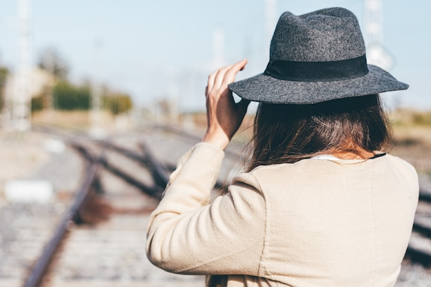 Rear view of a woman in beige raincoat and hat on abandoned railroad tracks.