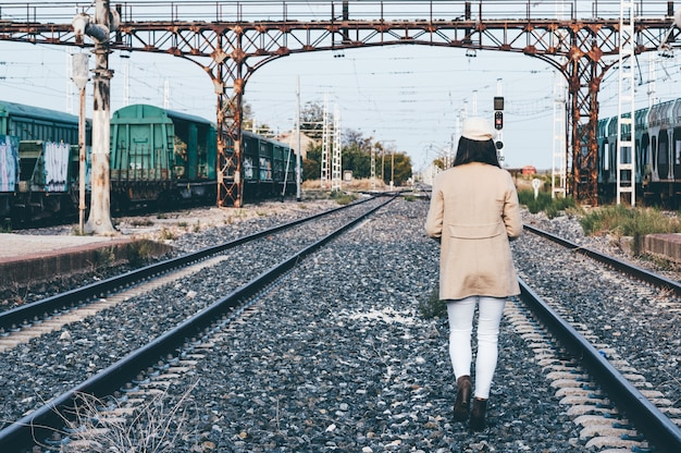 Rear view of a woman dressed with a beret and beige jacket walking across a railroad.