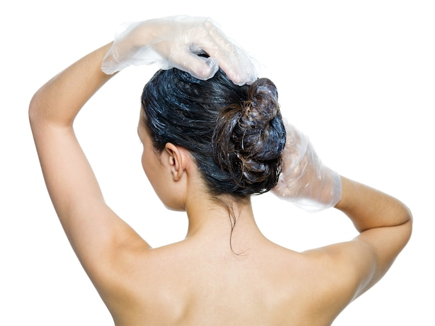 Rear view of woman dyeing hairs isolated on white