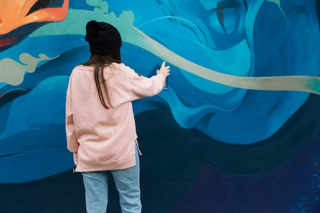 Rear view of woman hand drawing graffiti with spray paint