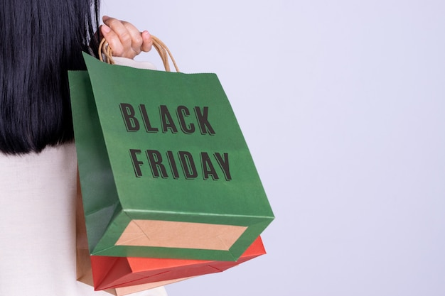 Rear view of woman holding black friday shopping bag. black friday concept with copy space.