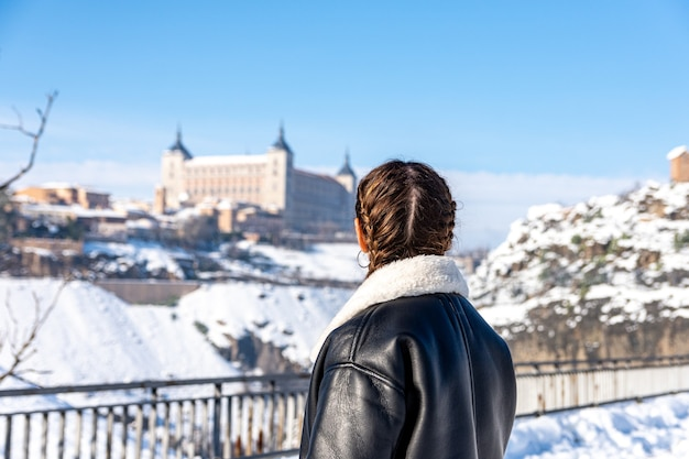 Rear view of a woman looking at the snow city of toledo. snow landscape.