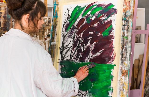 Rear view of woman painting on messy canvas at workshop