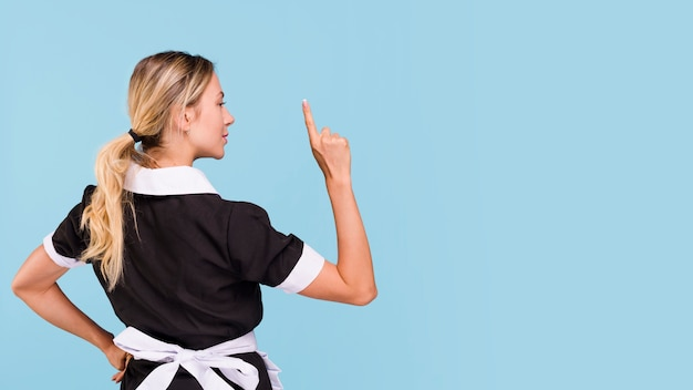 Rear view of woman pointing upwards standing against blue background