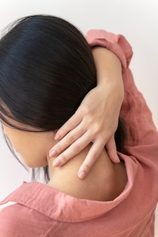 Vista posteriore di una donna che mette i suoi lunghi capelli in su