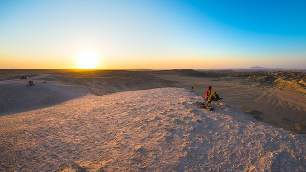 Rear view of woman sitting on rocks and looking at expansive view over the scenic namib desert at dusk time