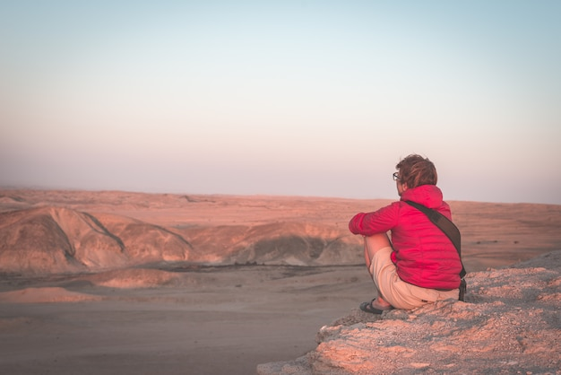 Rear view of woman sitting on rocks and looking at expansive view over the scenic namib desert at dusk time.